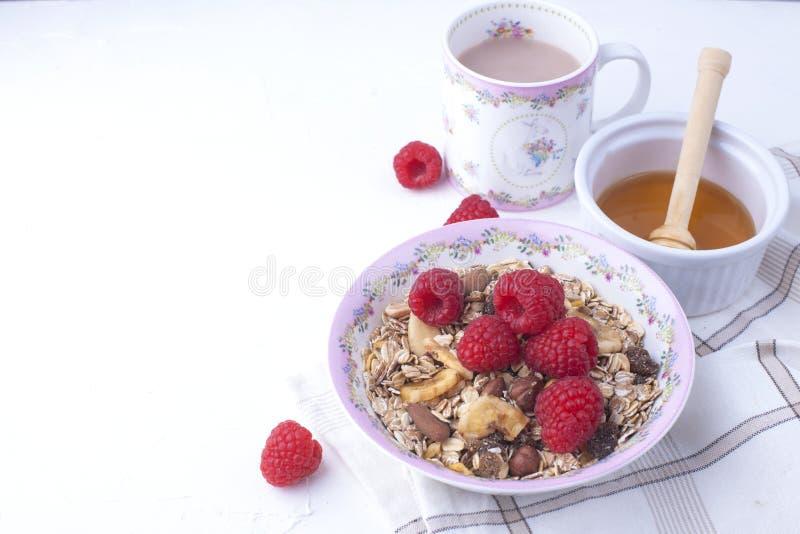 Εύγευστο και υγιές πρόγευμα σε ένα άσπρο υπόβαθρο Κουάκερ oatmeal, σμέουρο, μέλι, καφές για μια καλημέρα ελεύθερος στοκ φωτογραφία