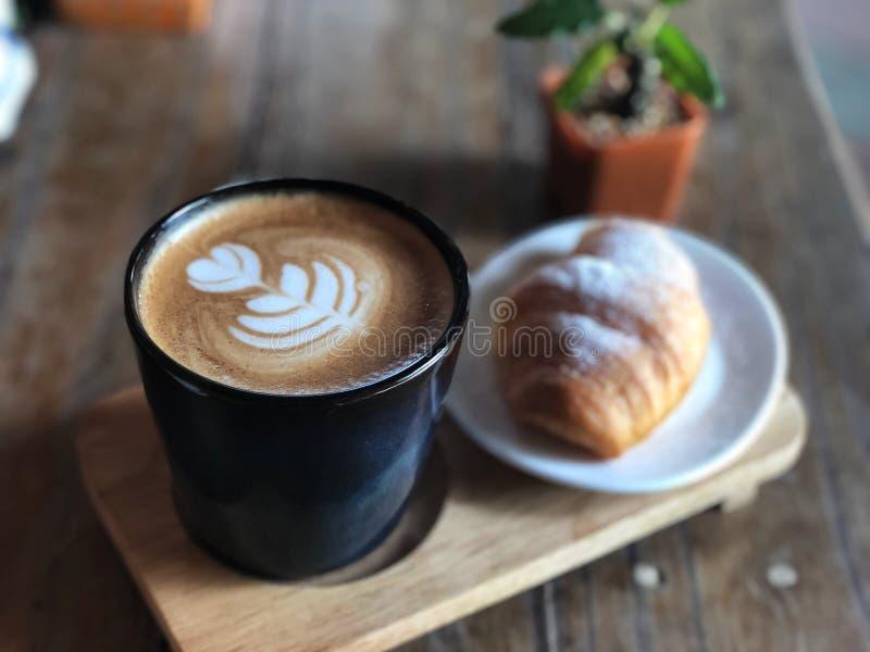 Εύγευστο πρόγευμα  Καφές τέχνης Latte αγάπης καρδιών φλυτζάνι και Croissant που ολοκληρώνεται στο μαύρο με τη ζάχαρη τήξης στοκ εικόνες