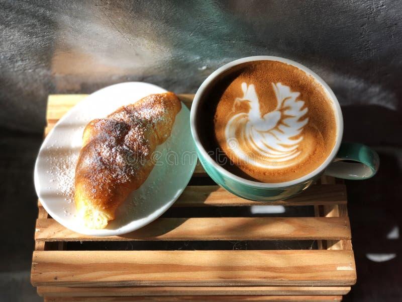 Εύγευστο πρόγευμα  καφές τέχνης Latte μορφής κύκνων στο πράσινα και άσπρα φλυτζάνι και Croissant στοκ φωτογραφίες με δικαίωμα ελεύθερης χρήσης