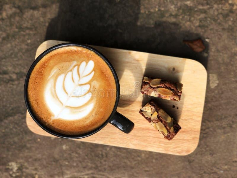 Εύγευστο πρόγευμα  Καφές τέχνης Latte φλυτζάνι και Brownie που ολοκληρώνεται στο μαύρο το αμύγδαλο που τεμαχίζεται με στοκ φωτογραφίες