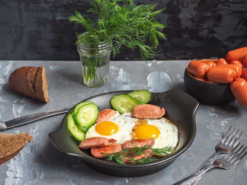 Εύγευστο πρόγευμα των ανακατωμένων αυγών και των λουκάνικων σε ένα μαύρο πιάτο με τις φέτες του φρέσκου αγγουριού σε έναν ξύλινο  στοκ εικόνες
