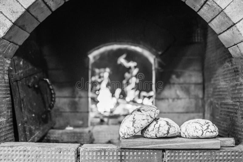 Εύγευστο πρόσφατα ψημένο ψωμί στο υπόβαθρο ο φούρνος και οι άνθρακες στην πυρκαγιά στοκ φωτογραφία