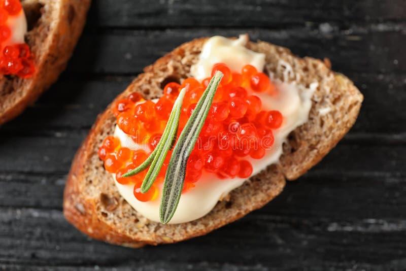 Εύγευστο σάντουιτς με το κόκκινο χαβιάρι στον ξύλινο πίνακα, κινηματογράφηση σε πρώτο πλάνο στοκ φωτογραφίες