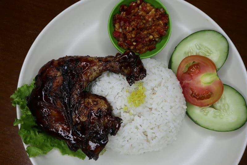 Εύγευστο ψημένο κοτόπουλο σε ένα πιάτο με τη σάλτσα τσίλι στοκ εικόνες