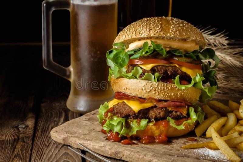 Εύγευστο burger βόειου κρέατος με τα τσιπ και μπύρα στον ξύλινο πίνακα στοκ φωτογραφία