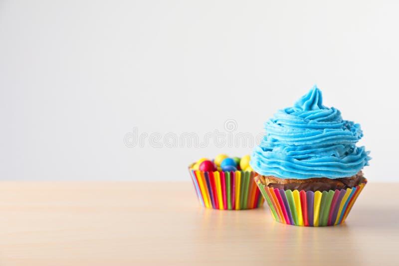 Εύγευστο cupcake με τις καραμέλες στον ελαφρύ ξύλινο πίνακα στοκ φωτογραφίες