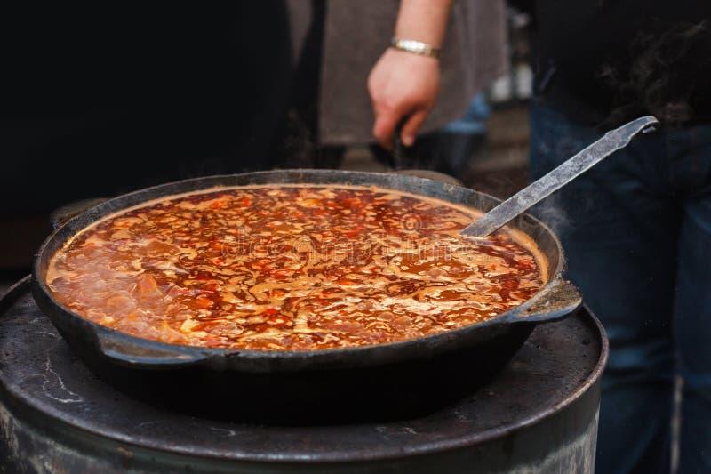Εύγευστο goulash στο μεγάλο κύπελλο με το κουτάλι στην ανοικτή σχάρα, υπαίθρια στοκ φωτογραφία