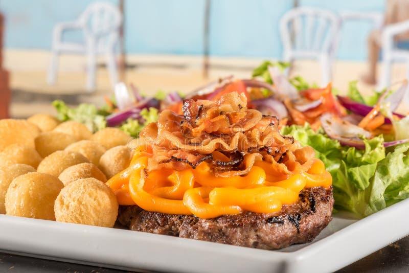 Εύγευστο Hambúrguer με το μπέϊκον και το τυρί Cheddar στοκ εικόνα