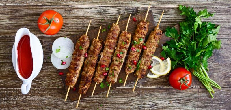 Εύγευστο lula kebab σε έναν ξύλινο πίνακα Τεμαχισμένο κρέας στα ξύλινα οβελίδια, που ψήνονται στη σχάρα Ανατολική κουζίνα r στοκ φωτογραφία με δικαίωμα ελεύθερης χρήσης