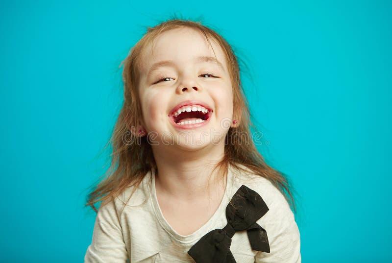Εύθυμα γέλια μικρών κοριτσιών στο μπλε υπόβαθρο στοκ εικόνες