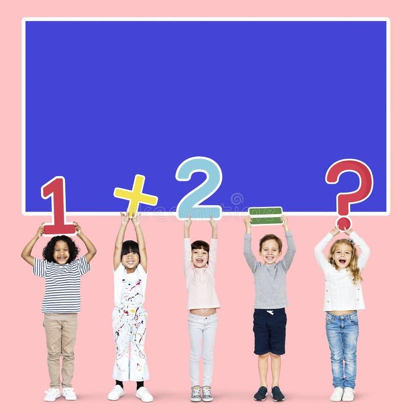 Εύθυμα διαφορετικά παιδιά που μαθαίνουν τα μαθηματικά στοκ εικόνα