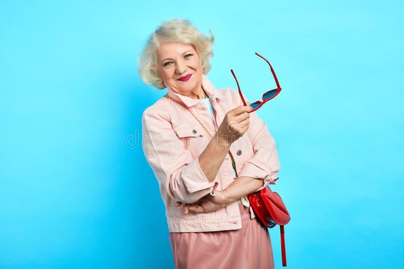 Εύθυμα ευτυχή ξανθά γυαλιά ηλίου εκμετάλλευσης ηλικιωμένων κυριών και κατοχή ενός υπολοίπου στοκ εικόνα με δικαίωμα ελεύθερης χρήσης