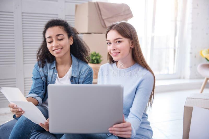 Εύθυμα κορίτσια που θέτουν ψωνίζοντας on-line για το χρώμα τοίχων στοκ φωτογραφία με δικαίωμα ελεύθερης χρήσης