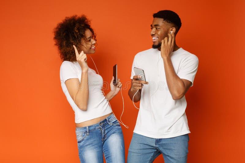 Εύθυμα μαύρα millennials που ακούνε τη μουσική με τα νέα ακουστικά στοκ φωτογραφίες