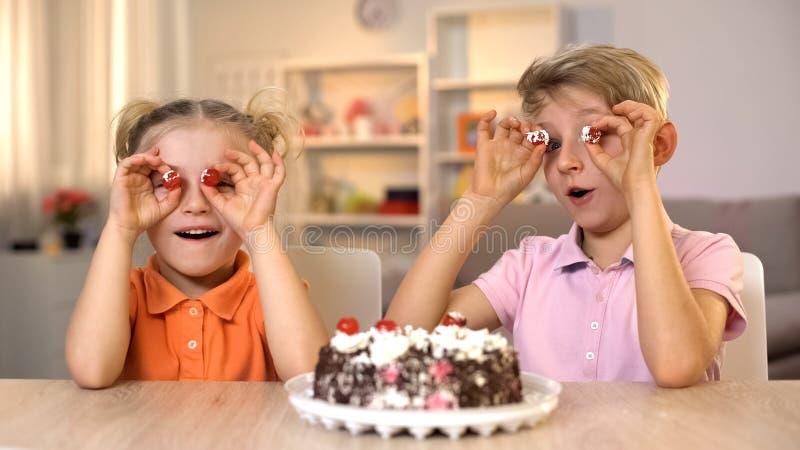 Εύθυμα μπροστινά μάτια κερασιών κέικ εκμετάλλευσης αδελφών και αδελφών, που παίζουν από κοινού στοκ φωτογραφίες