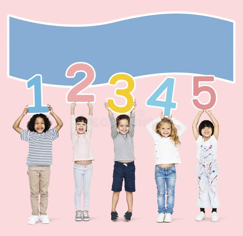 Εύθυμα παιδιά που κρατούν τους αριθμούς ένα έως πέντε στοκ φωτογραφία με δικαίωμα ελεύθερης χρήσης