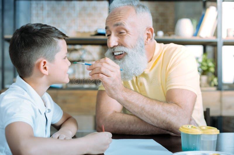 Εύθυμα granddad και παιδί που αστειεύονται χρωματίζοντας στο σπίτι στοκ εικόνες