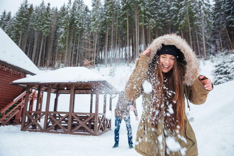 Εύθυμες νέες χιονιές παιχνιδιού ζευγών και κατοχή της διασκέδασης στοκ φωτογραφίες