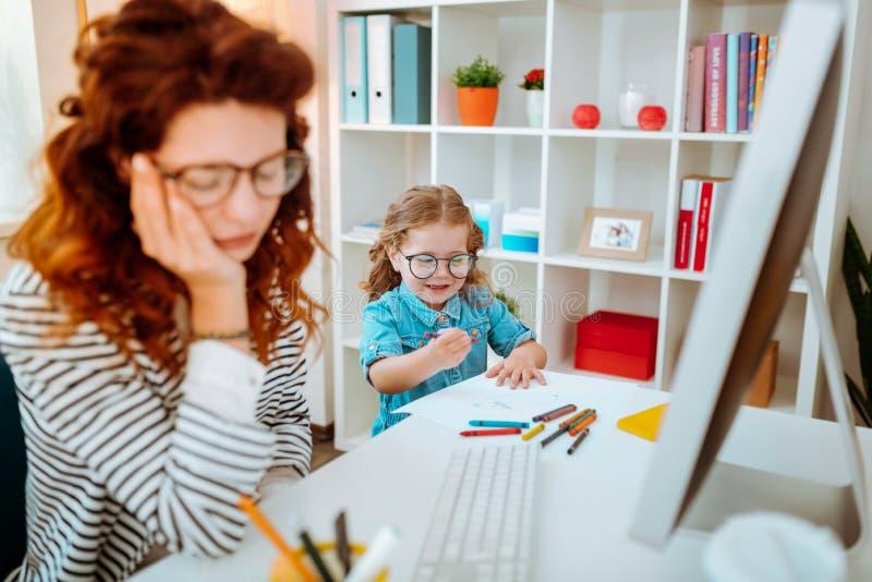 Εύθυμες χρωματίζοντας εικόνες κορών που στέκονται κοντά στην εργαζόμενη μητέρα στοκ εικόνες