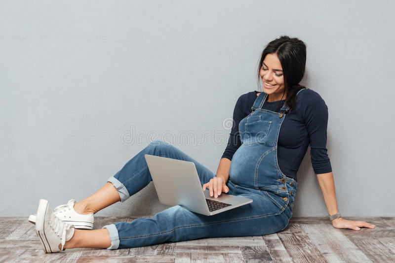 Εύθυμη έγκυος γυναικεία συνεδρίαση στο πάτωμα που χρησιμοποιεί το φορητό προσωπικό υπολογιστή στοκ εικόνα