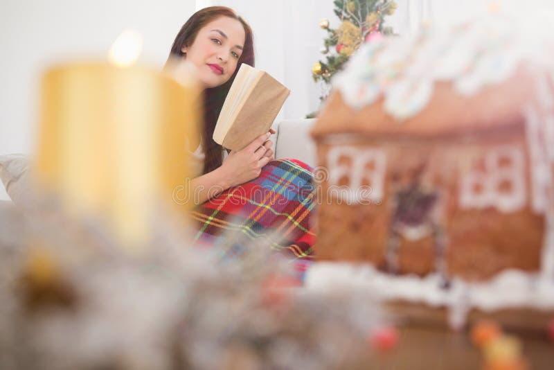 Εύθυμη ανάγνωση brunette στον καναπέ με την κάλυψη στα Χριστούγεννα στοκ φωτογραφία με δικαίωμα ελεύθερης χρήσης