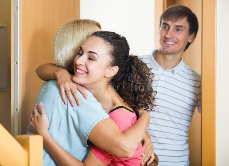 Εύθυμη ανώτερη γυναίκα που χαιρετά τα ενήλικα παιδιά που έρχονται με την επίσκεψη στοκ φωτογραφίες