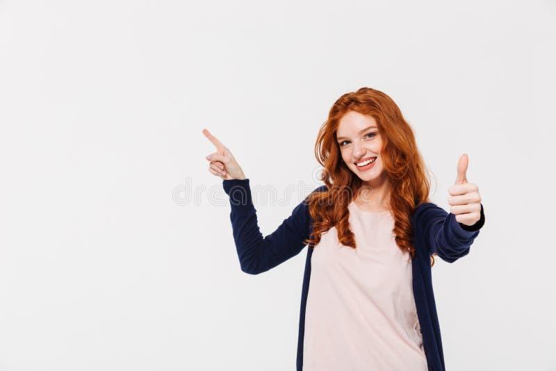 Εύθυμη αρκετά νέα redhead κυρία που παρουσιάζει αντίχειρες δείχνοντας στοκ φωτογραφίες
