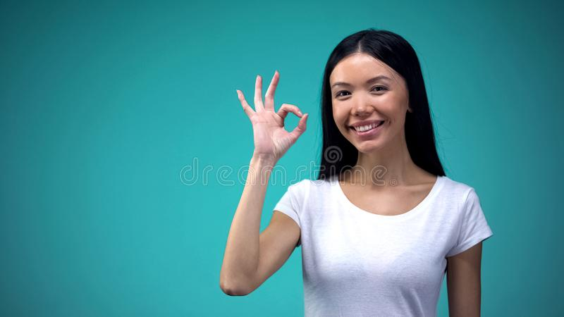 Εύθυμη ασιατική γυναίκα που παρουσιάζει εντάξει σημάδι, που απομονώνεται στο μπλε υπόβαθρο, πρότυπο στοκ εικόνες με δικαίωμα ελεύθερης χρήσης