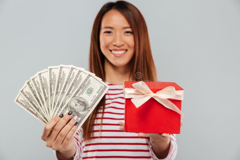 Εύθυμη ασιατική γυναίκα στο πουλόβερ που παρουσιάζει τα χρήματα και το δώρο στοκ φωτογραφία με δικαίωμα ελεύθερης χρήσης