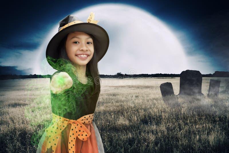 Εύθυμη ασιατική μαγισσών παιδιών κοριτσιών δύναμη ράβδων χρήσης μαγική στοκ φωτογραφία με δικαίωμα ελεύθερης χρήσης