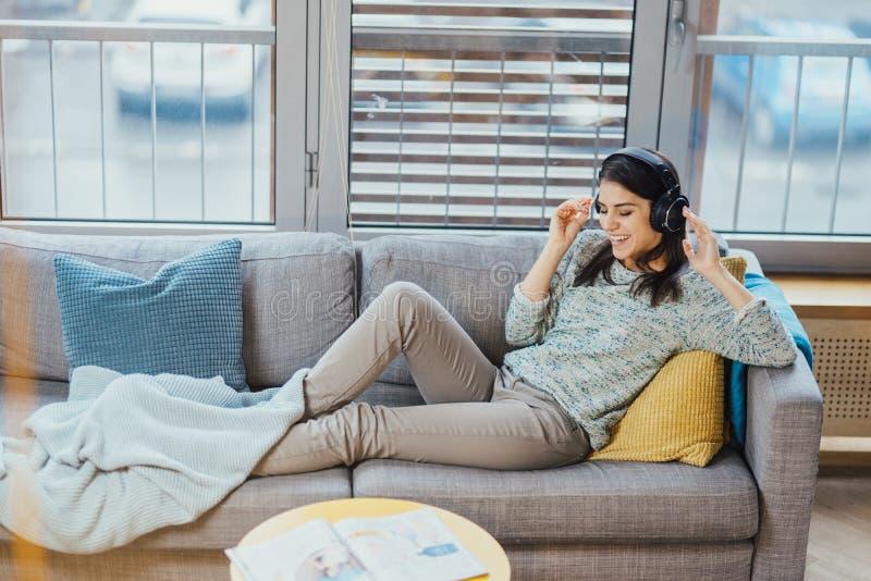 Εύθυμη γυναίκα που ακούει τη μουσική με τα μεγάλα ακουστικά και το τραγούδι Απολαμβάνοντας το άκουσμα στη μουσική, μουσικοθεραπεί στοκ φωτογραφία
