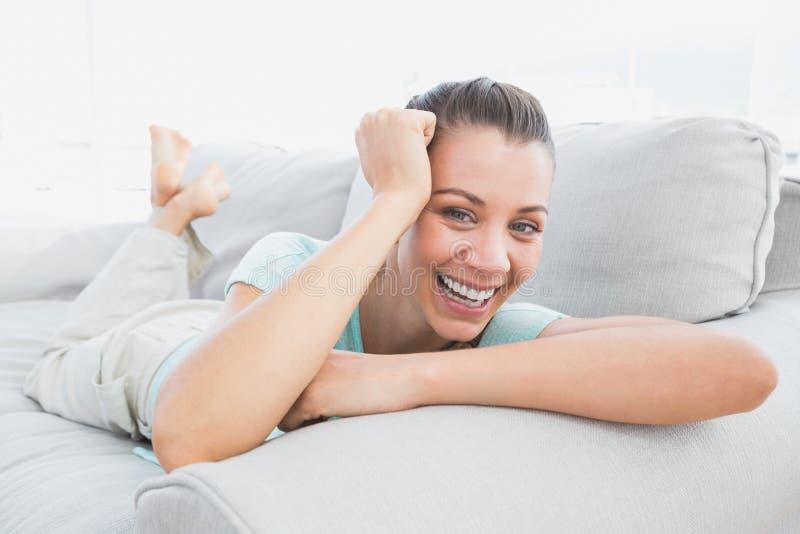 Εύθυμη γυναίκα που βρίσκεται στον καναπέ που χαμογελά στη κάμερα στοκ εικόνες με δικαίωμα ελεύθερης χρήσης