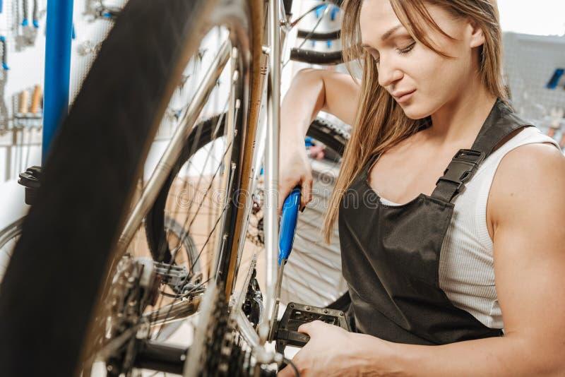 Εύθυμη γυναίκα που επισκευάζει το πεντάλι στο εργαστήριο στοκ φωτογραφία με δικαίωμα ελεύθερης χρήσης