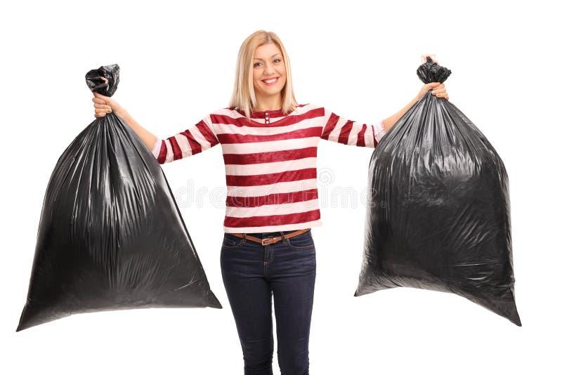 Εύθυμη γυναίκα που κρατά δύο τσάντες απορριμμάτων στοκ εικόνες