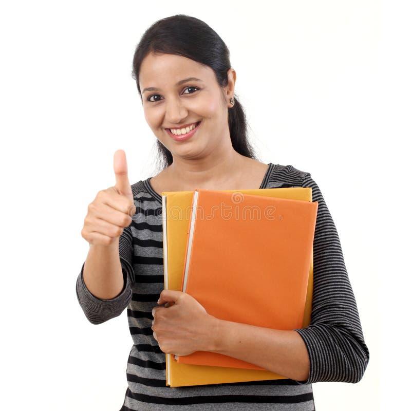 Εύθυμη γυναίκα σπουδαστής με τους αντίχειρες επάνω στη χειρονομία στοκ εικόνα με δικαίωμα ελεύθερης χρήσης