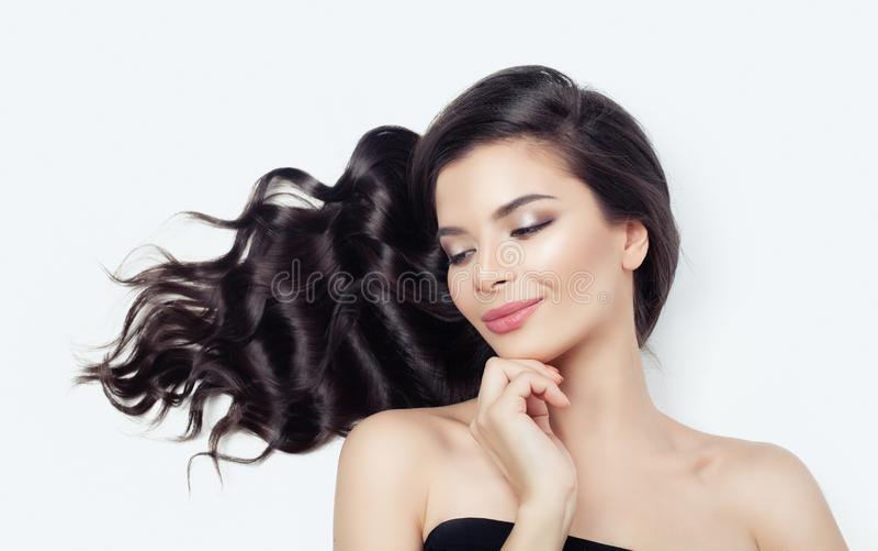Εύθυμη γυναίκα στο άσπρο υπόβαθρο Μακριά σγουρή τρίχα, φυσικό makeup, χαριτωμένο χαμόγελο στοκ φωτογραφία