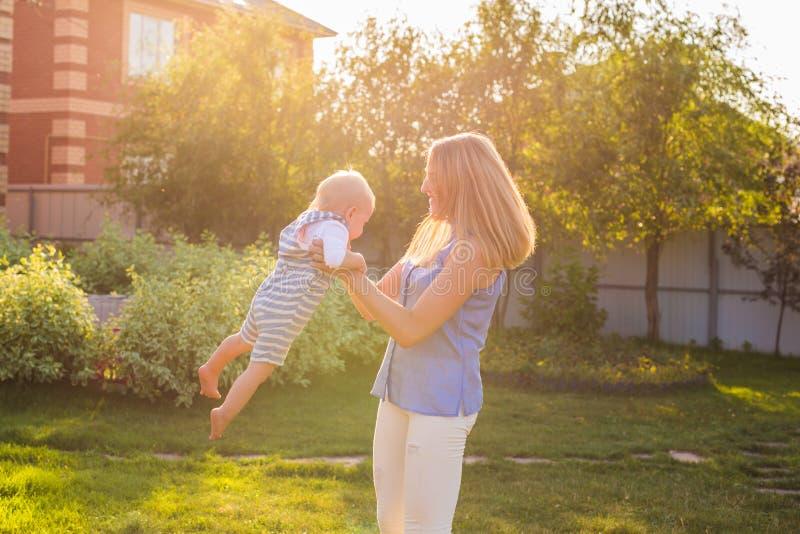 Εύθυμη γυναίκα στο παιχνίδι κήπων με το γιο μωρών της στοκ εικόνες με δικαίωμα ελεύθερης χρήσης