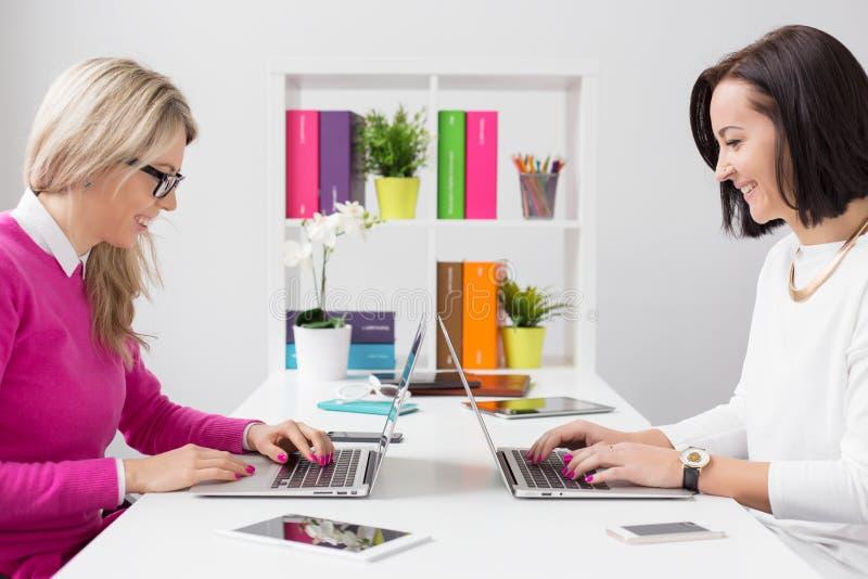 Εύθυμη γυναίκα δύο που εργάζεται με τους υπολογιστές στο γραφείο στοκ εικόνα