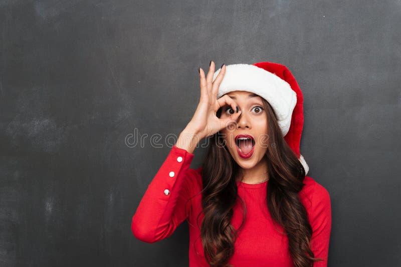 Εύθυμη γυναίκα brunette στο κόκκινο καπέλο μπλουζών και Χριστουγέννων στοκ εικόνες