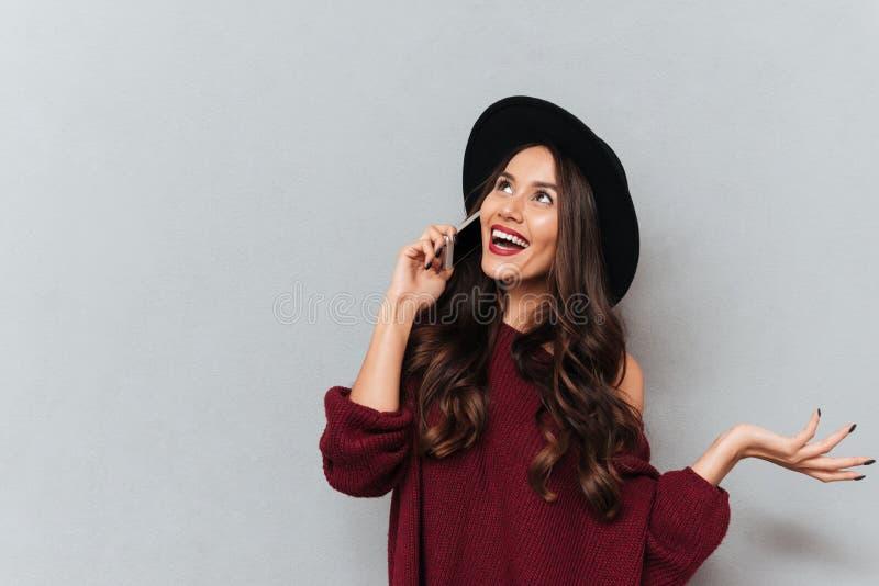 Εύθυμη γυναίκα brunette στο πουλόβερ και καπέλο που μιλά από το smartphone στοκ φωτογραφίες με δικαίωμα ελεύθερης χρήσης