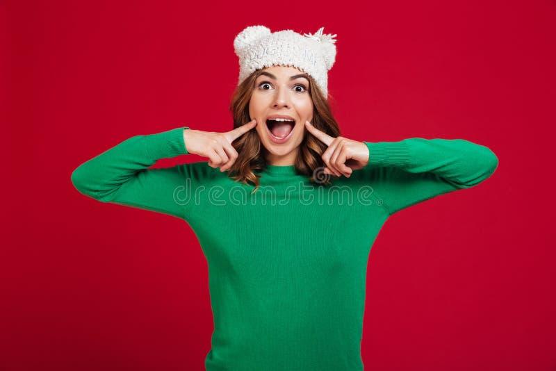 Εύθυμη γυναίκα brunette στο πουλόβερ και το αστείο καπέλο στοκ εικόνες με δικαίωμα ελεύθερης χρήσης