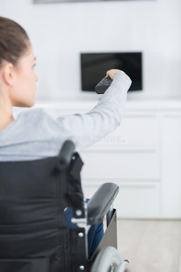 Εύθυμη εκτός λειτουργίας ανώτερη τηλεόραση προσοχής γυναικών στο καθιστικό στοκ φωτογραφίες