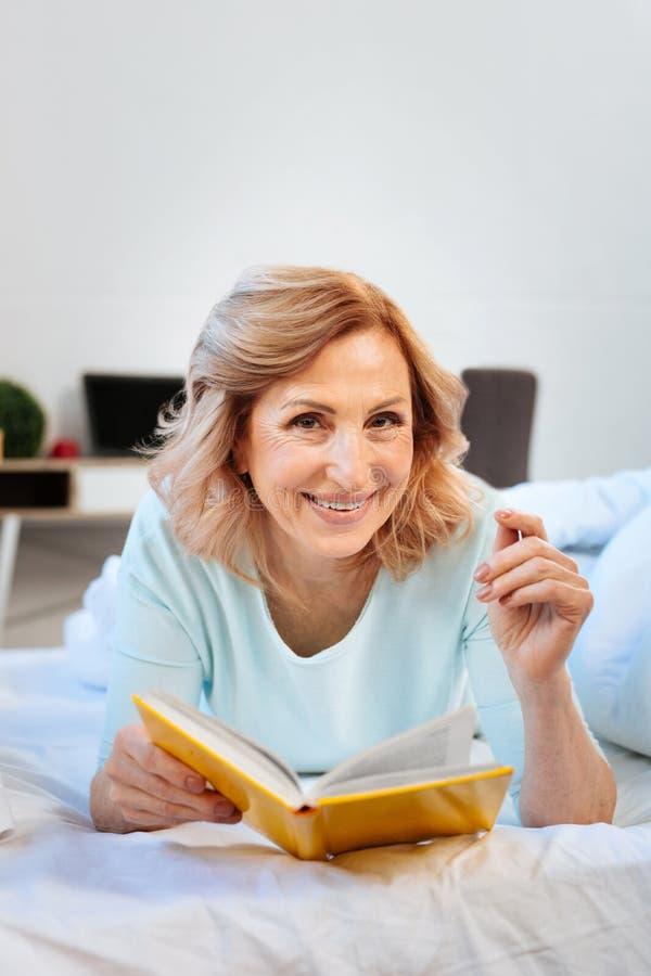 Εύθυμη ελαφρύς-μαλλιαρή γυναίκα που στηρίζεται στο κρεβάτι της και που διαβάζει το ενδιαφέρον βιβλίο στοκ εικόνες