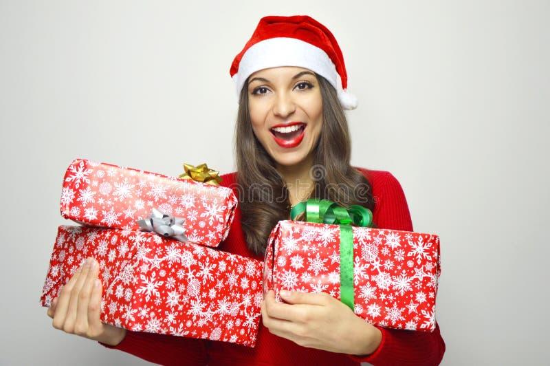 Εύθυμη ελκυστική γυναίκα που χαμογελά με τα χριστουγεννιάτικα δώρα εκμετάλλευσης καπέλων Άγιου Βασίλη στο άσπρο υπόβαθρο στοκ εικόνες με δικαίωμα ελεύθερης χρήσης
