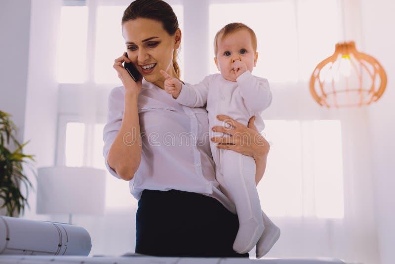 Εύθυμη επιχειρηματίας που κρατά ένα μωρό και που μιλά στο τηλέφωνο στοκ εικόνες