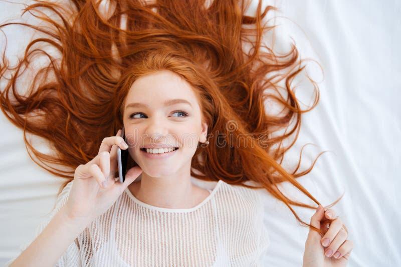 Εύθυμη εύθυμη γυναίκα που μιλά στο τηλέφωνο κυττάρων στο κρεβάτι στοκ εικόνα