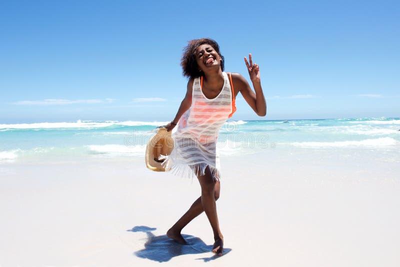 Εύθυμη ελκυστική νέα αφρικανική γυναίκα που απολαμβάνει τον περίπατο στην παραλία στοκ εικόνες με δικαίωμα ελεύθερης χρήσης