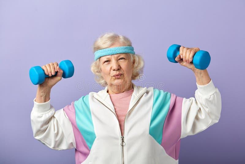 Εύθυμη ηλικιωμένη γυναίκα που ασκεί με ένα ζευγάρι των αλτήρων και του χαμόγελου στοκ φωτογραφία