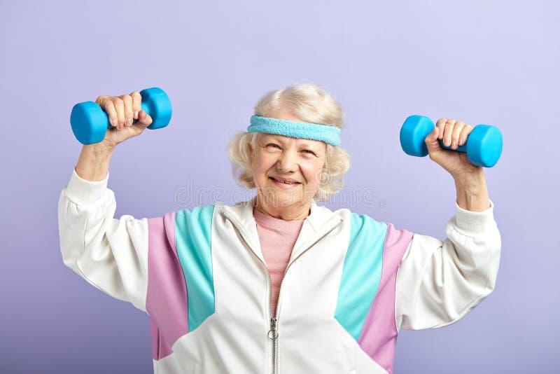 Εύθυμη ηλικιωμένη γυναίκα που ασκεί με ένα ζευγάρι των αλτήρων και του χαμόγελου στοκ εικόνες