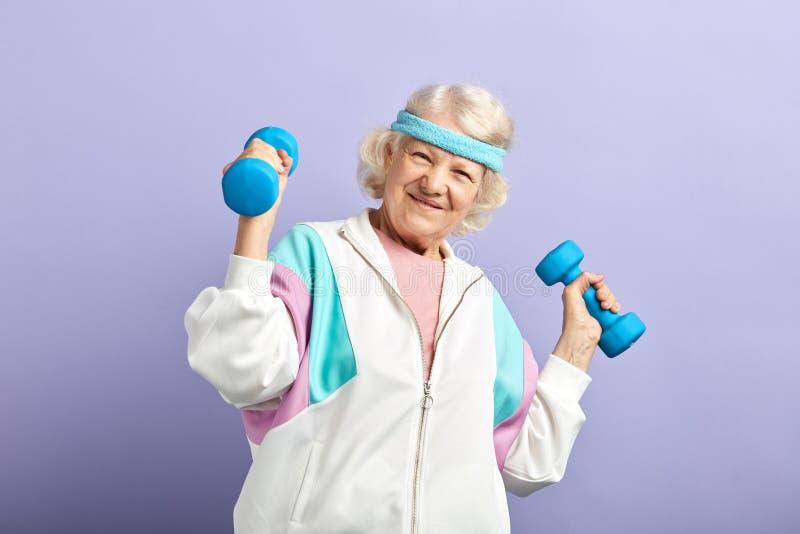 Εύθυμη ηλικιωμένη γυναίκα που ασκεί με ένα ζευγάρι των αλτήρων και του χαμόγελου στοκ φωτογραφία με δικαίωμα ελεύθερης χρήσης